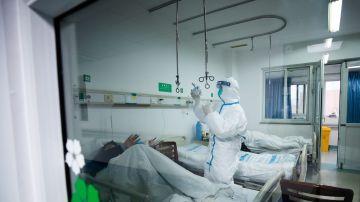 Un sanitario atendiendo a un paciente en un hospital de Wuhan, China