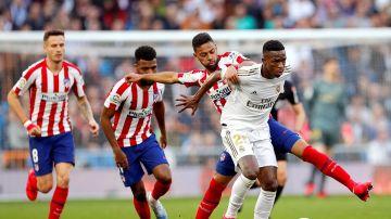 Los jugadores brasileños Vinícius Jr. (d) del Real Madrid y Renan Lodi del Atlético de Madrid, disputan un balón