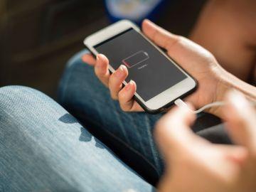 Imagen de archivo de una persona cargador su smartphone.