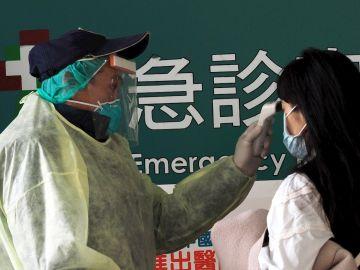 Imagen de un trabajador controlando la temperatura a una pasajera