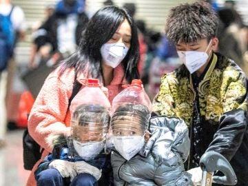 Imagen de unos dos niños con protecciones faciales improvisadas a partir de botellas de plástico para protegerse del coronavirus