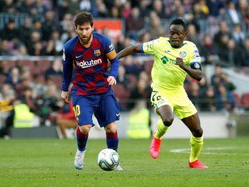 El delantero argentino Lionel Messi del Barcelona y el defensor togolés Djené Dakonam del Getafe