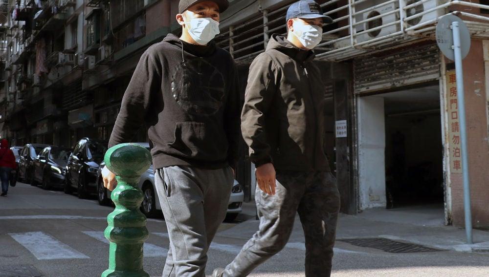 Dos personas pasean con mascarillas en Macao
