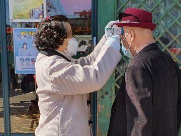 Imagen de dos personas con mascarillas para protegerse del coronavirus en Corea del Sur
