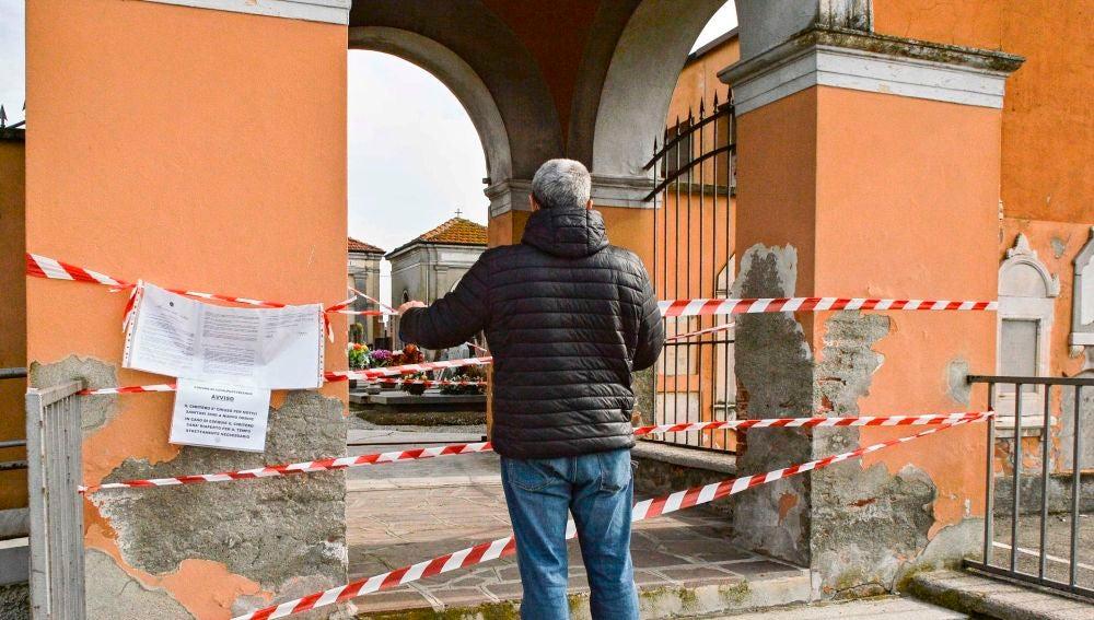 Un ciudadano observa un cementerio cerrado por el coronavirus