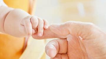 Imagen de archivo de un bebé cogiendo la mano de un adulto.