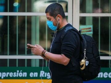 Coronavirus | Un hombre con mascarilla consulta su teléfono