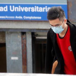 Un joven con mascarilla en el acceso a la estación de metro de Ciudad Universitaria, en Madrid