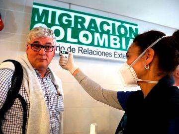 Funcionarios toman la temperatura de los ciudadanos que llegan al aeropuerto internacional El Dorado