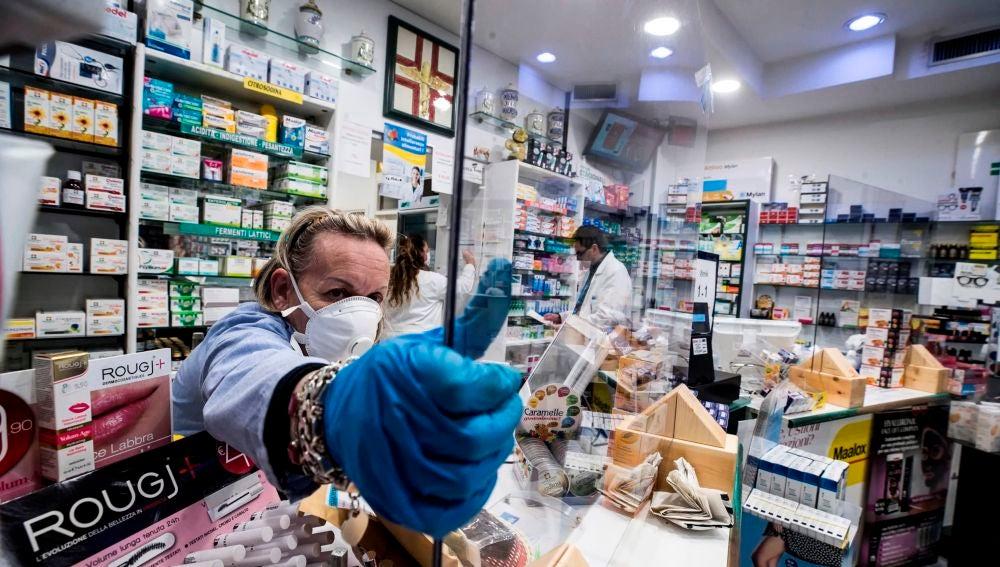 Una farmacia protege con plexiglás al personal durante el cierre de emergencia debido al brote de coronavirus en Roma