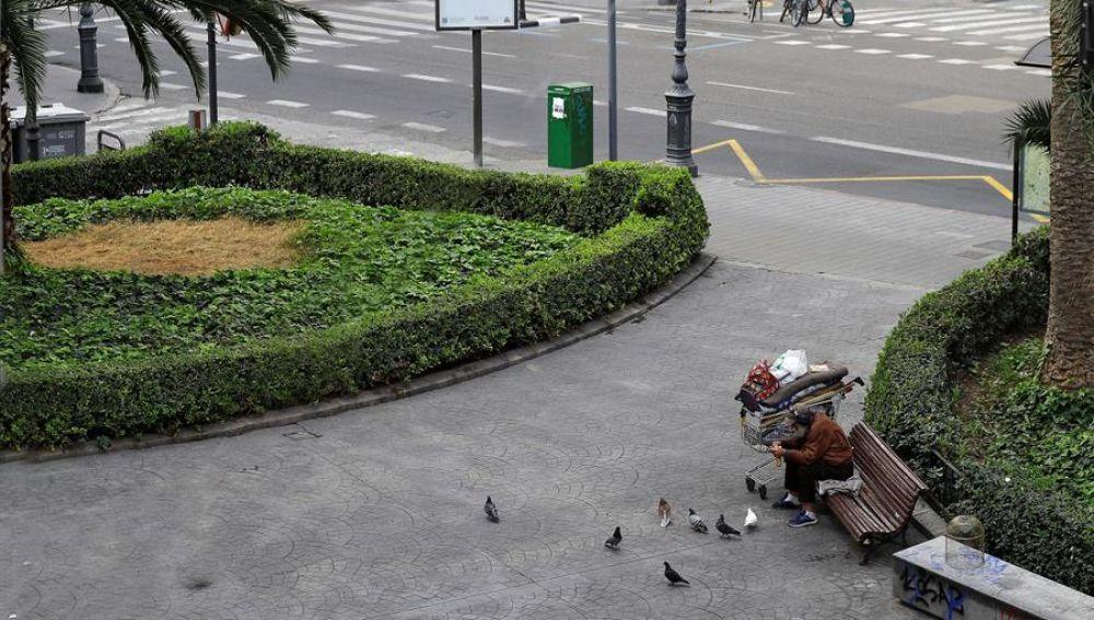 Un hombre sin hogar en Valencia, prácticamente vacía por el estado de alarma por el coronavirus