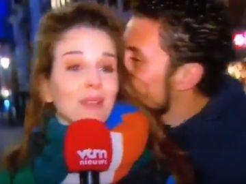 Un hombre besa a una reportera