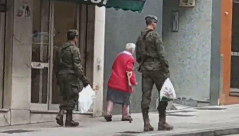 El momento en el que dos soldados llevan la compra a una anciana en Gijón