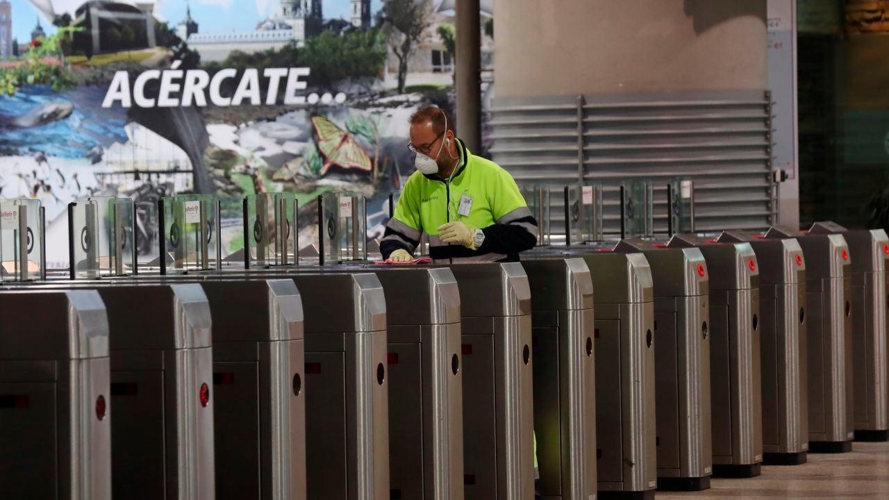 Un operario desinfecta los tornos del Cercanías en la estación de Atocha en Madrid
