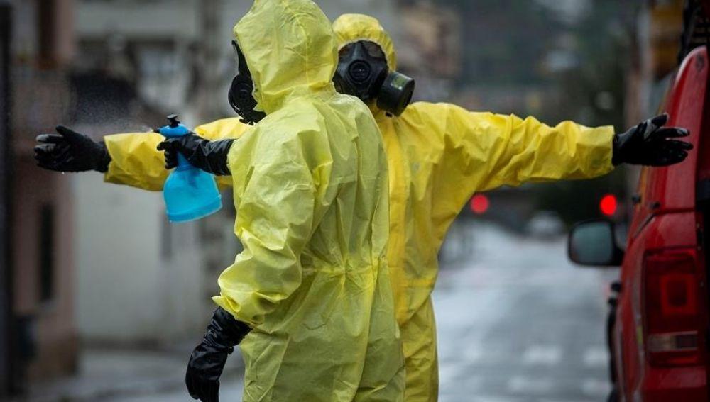 Miembros de la Unidad Militar de Emergencia se desinfectan tras trabajar