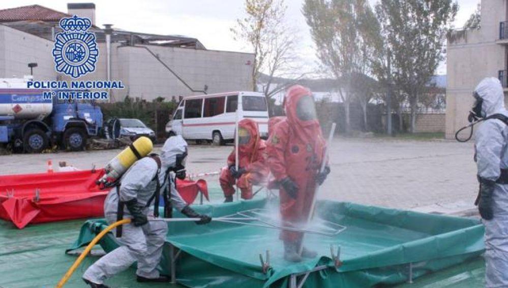 Un equipo de los TEDAX desinfectando a agentes de la Policía Nacional
