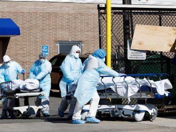 Profesionales sanitarios transportan fallecidos por coronavirus en una morgue temporal en Brooklyn