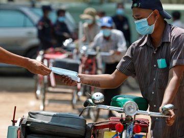 Un conductor recibe una mascarilla gratuita durante una donación de alimentos a personas con bajos ingresos en Myanmar