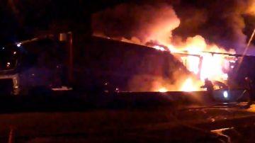 Los bomberos trabajan para detener el fuego desatado en uno de los camiones.