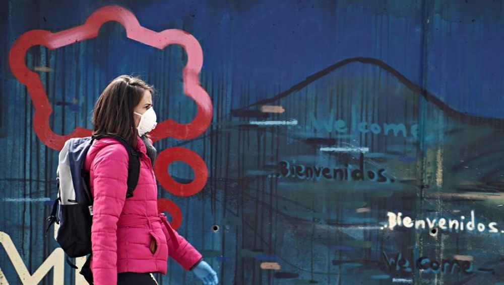 Una mujer con mascarilla y guantes camina por una calle de Ávila