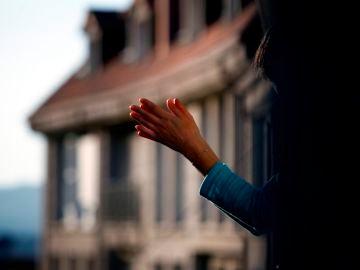 Imagen de una mujer aplaudiendo en un balcón durante la crisis por coronavirus