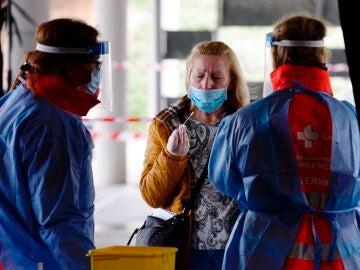 Le toman una muestra a una mujer para realizar el test del coronavirus