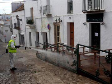 Un operario de limpieza desinfecta una terraza de un bar en Cádiz