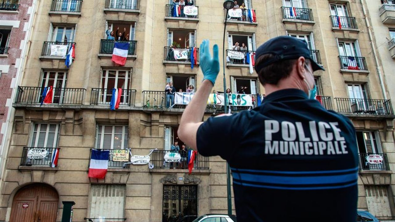 Un oficial de Policía aplaude frente a un edificio en Francia