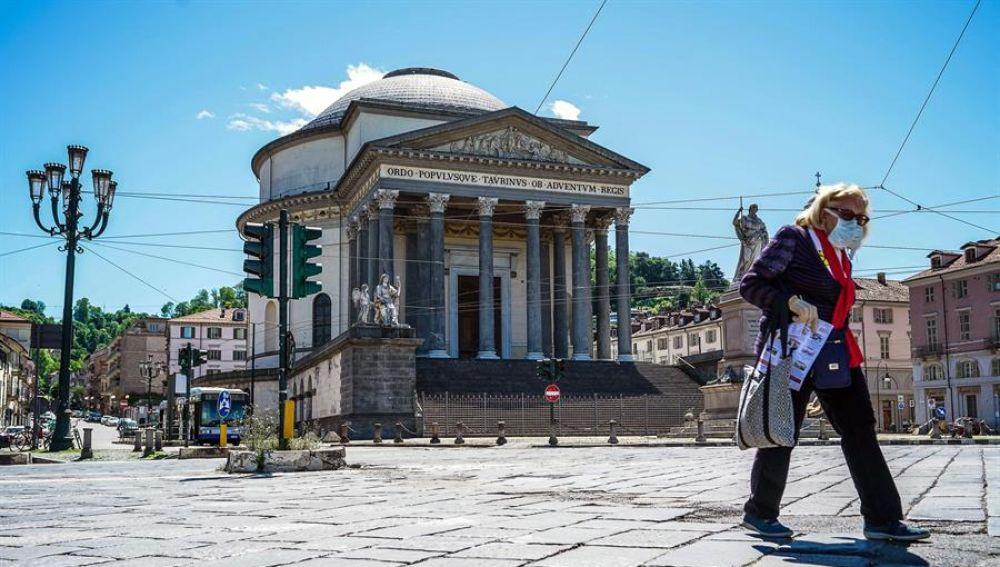 Una mujer protegida con mascarilla camina por las calles de Roma.