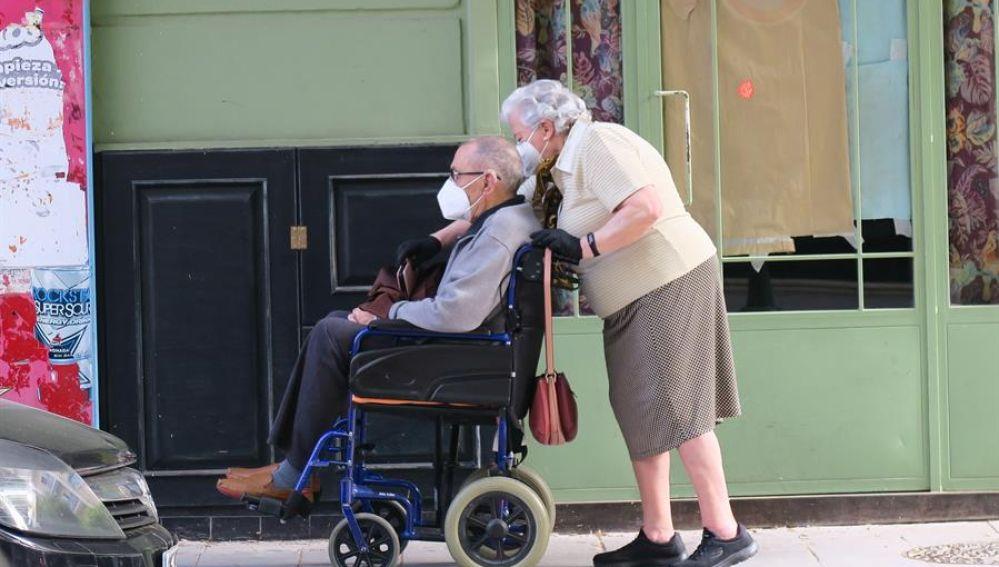 Una pareja de mayores pasea por una calle de Granada