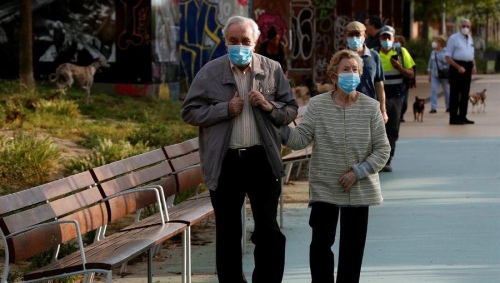 Una pareja protegida con mascarillas pasea por la Rambla Nova de Sants