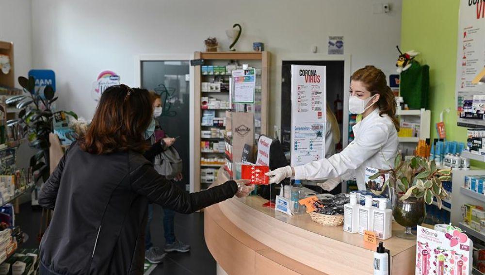 Una farmacéutica entrega una mascarilla en una farmacia madrileña.