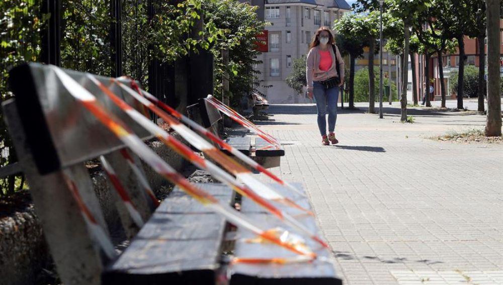 Una mujer pasea junto a unos bancos en Ponferrada
