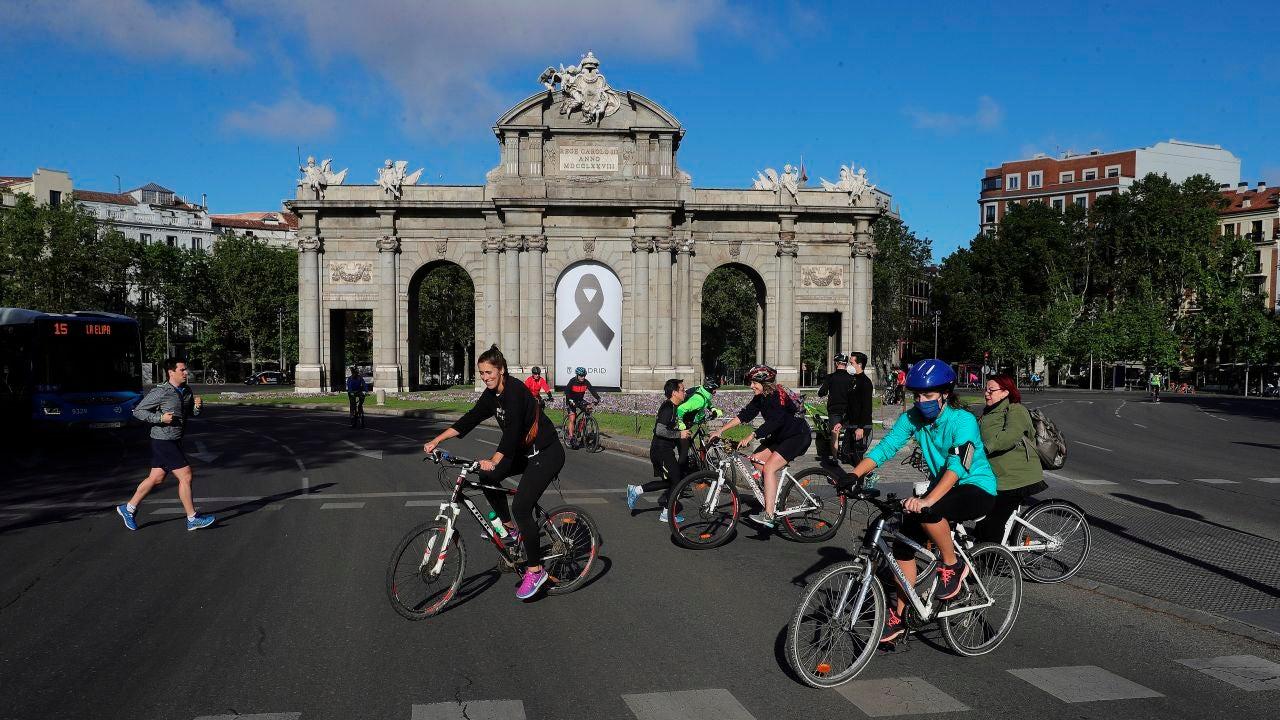 Vista de la Puerta de Alcalá con un crespón negro junto a la gente haciendo deporte en Madrid