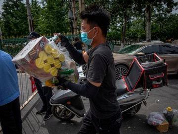 Un repartidor en Pekín con mascarilla