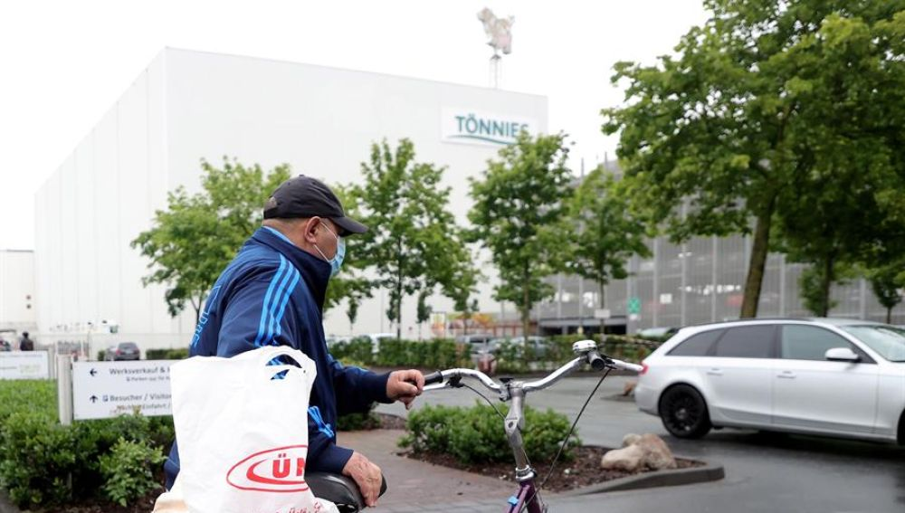 Un empleado de la planta cárnica de Gütersloh llega a la sede con mascarilla.,