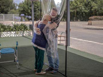 Una interna en una residencia de mayores abraza a su hijo a través de un plástico tras meses de separación por el Covid