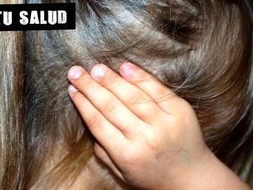 Imagen de archivo de una niña con la mano en la oreja