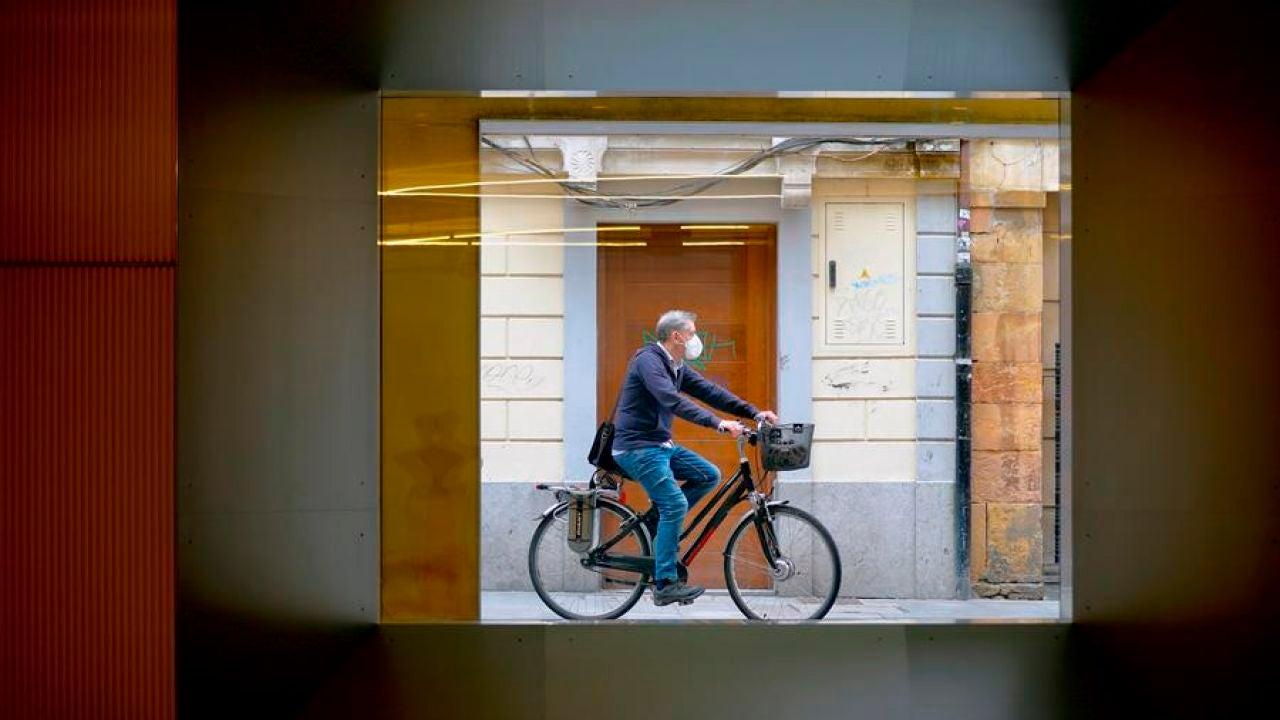 Un hombre con mascarilla pasea en bicicleta