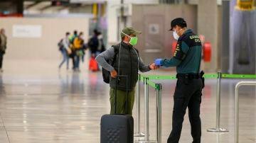 Un pasajero con mascarilla a su llegada al Aeropuerto de Barajas