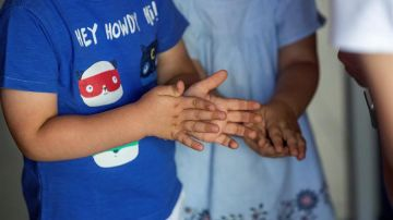 Dos niños de desinfectan las manos con gel hidroalcohólico
