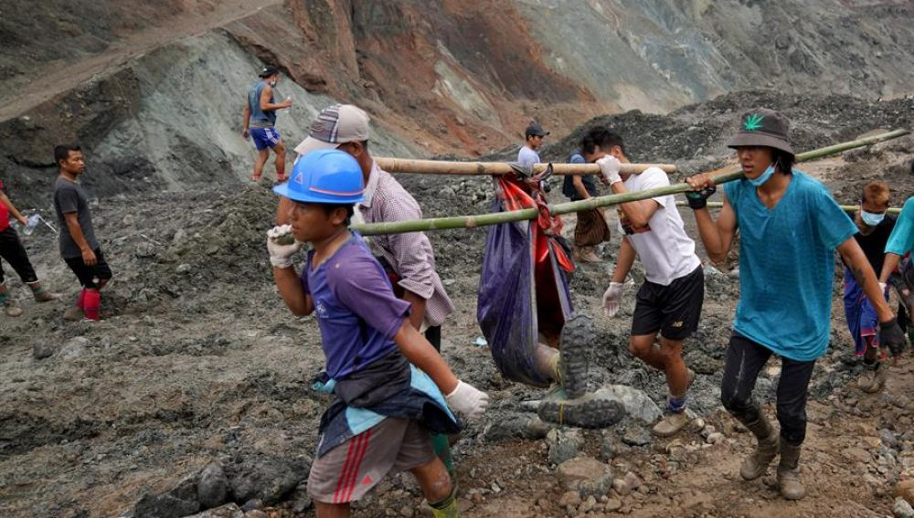 Voluntarios llevan el cuerpo de una víctima después de un deslizamiento de tierra en una mina de jade en Hpakant, estado de Kachin, Myanmar,