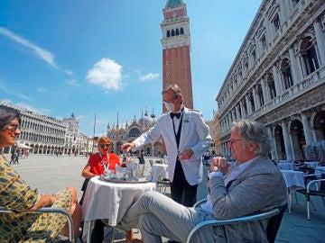 Un camarero atiende a varios clientes en una terraza