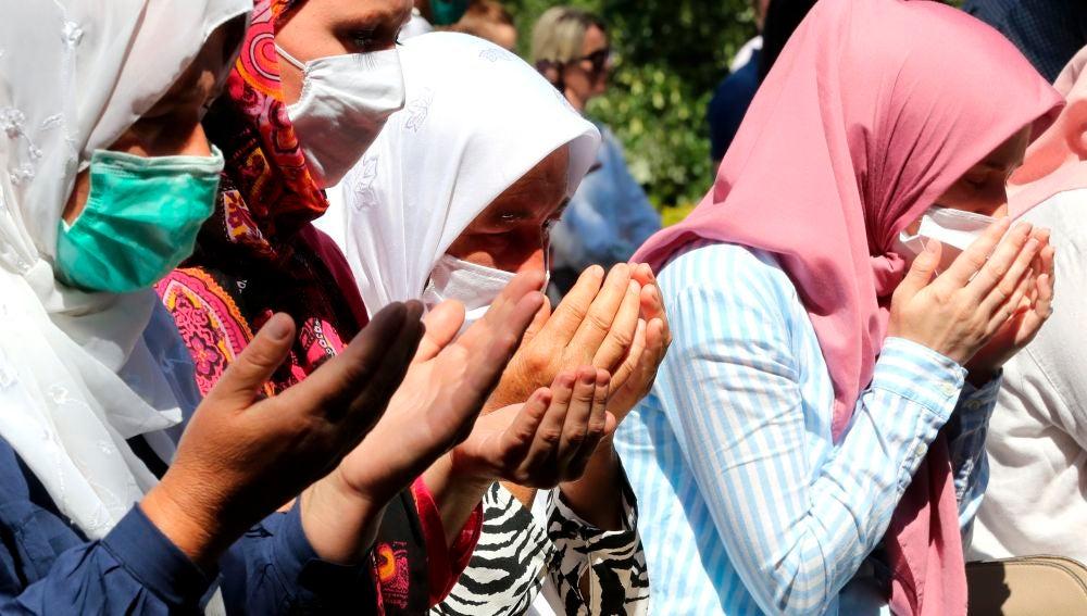 Mujeres rezando en el 25 aniversario de la masacre