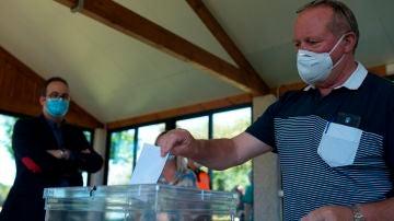 El coordinador de prevención de las elecciones de la Xunta, Emilio de la Iglesia, observa una votación simulada durante la visita a un colegio electoral de Galicia