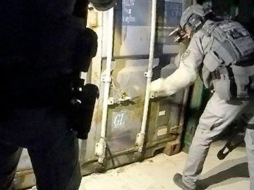 Miembros de la Policía holandesa examinan uno de los contenedores usados como prisiones y localizados durante una operación policial