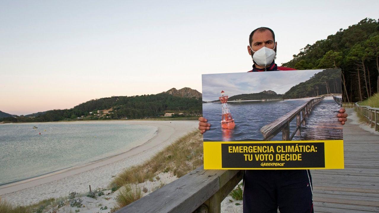 Un activista de Greenpeace sujeta un cartel en el que alerta de la emergencia climática