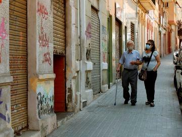 Una mujer acomapaña a su padre por una calle del barrio de la Torrassa