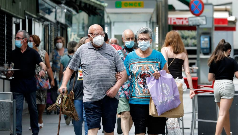 Varias personas en los alrededores del mercado del barrio de Collblanc de L'Hospitalet (Barcelona)