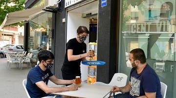 Imagen de dos jóvenes con mascarilla en una terraza de Lleida